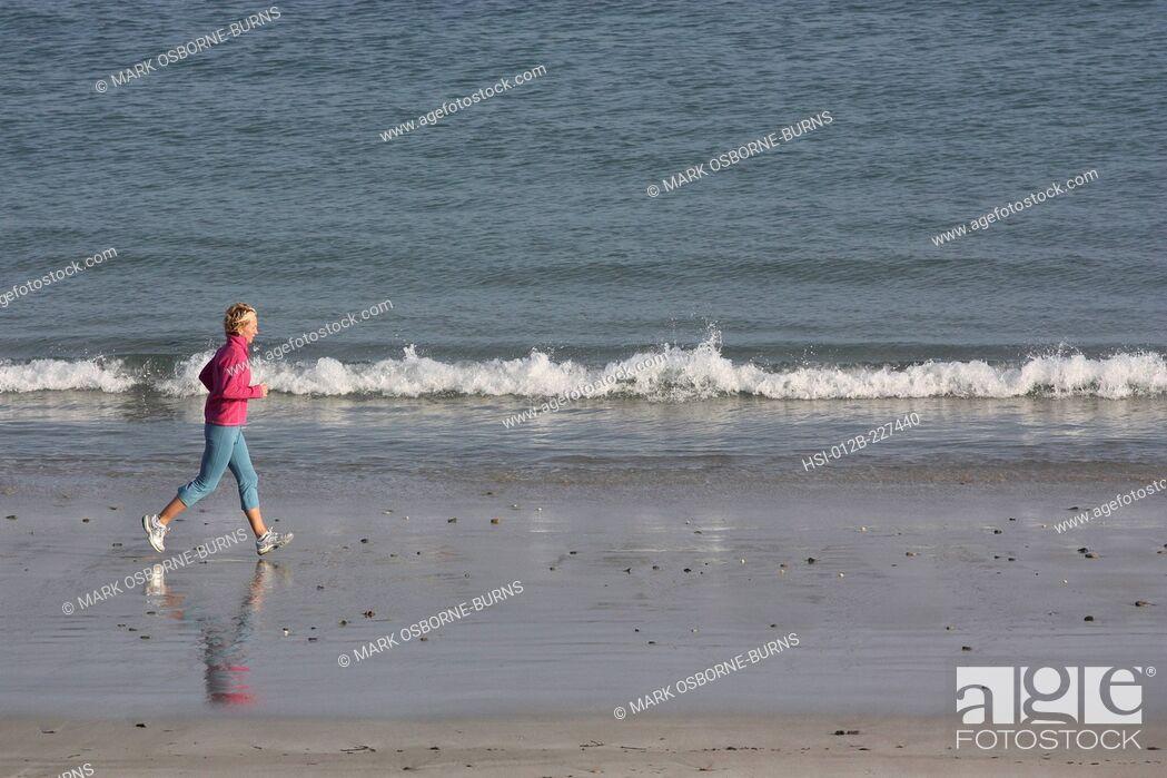 Stock Photo: Blonde woman outdoors. Jogging along beach.
