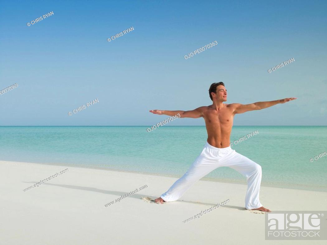Stock Photo: Man in warrior 2 yoga pose on beach.