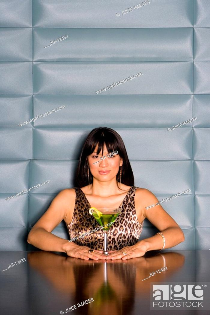 Stock Photo: Young woman at table with cocktail, portrait.