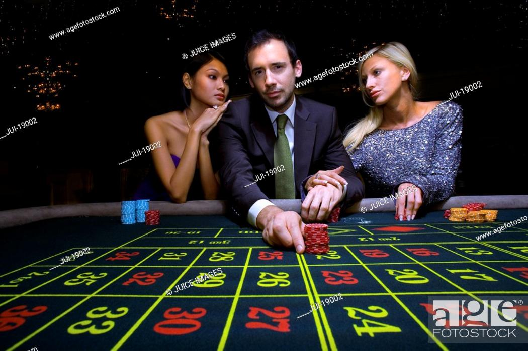 Stock Photo: Man flanked by women, gambling at roulette table, portrait, low angle view.