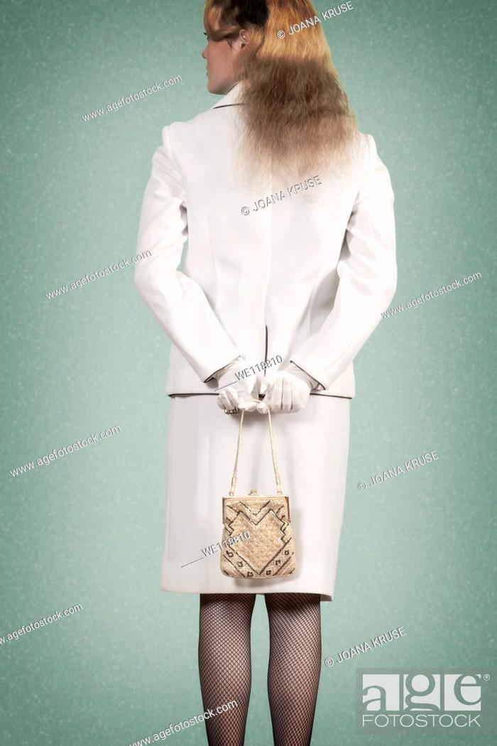 Stock Photo: a woman in a vintage skirt suit is holding a handbag.