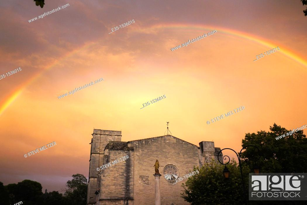 Stock Photo: After a rainstorm a rainbow appears over the 13th century Church of St. Saturnin on the outskirts of Pezenas, France.