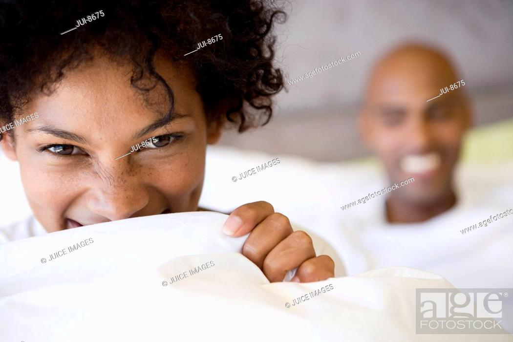 Stock Photo: Young woman biting into pillow, portrait, close-up, young man smiling in background.