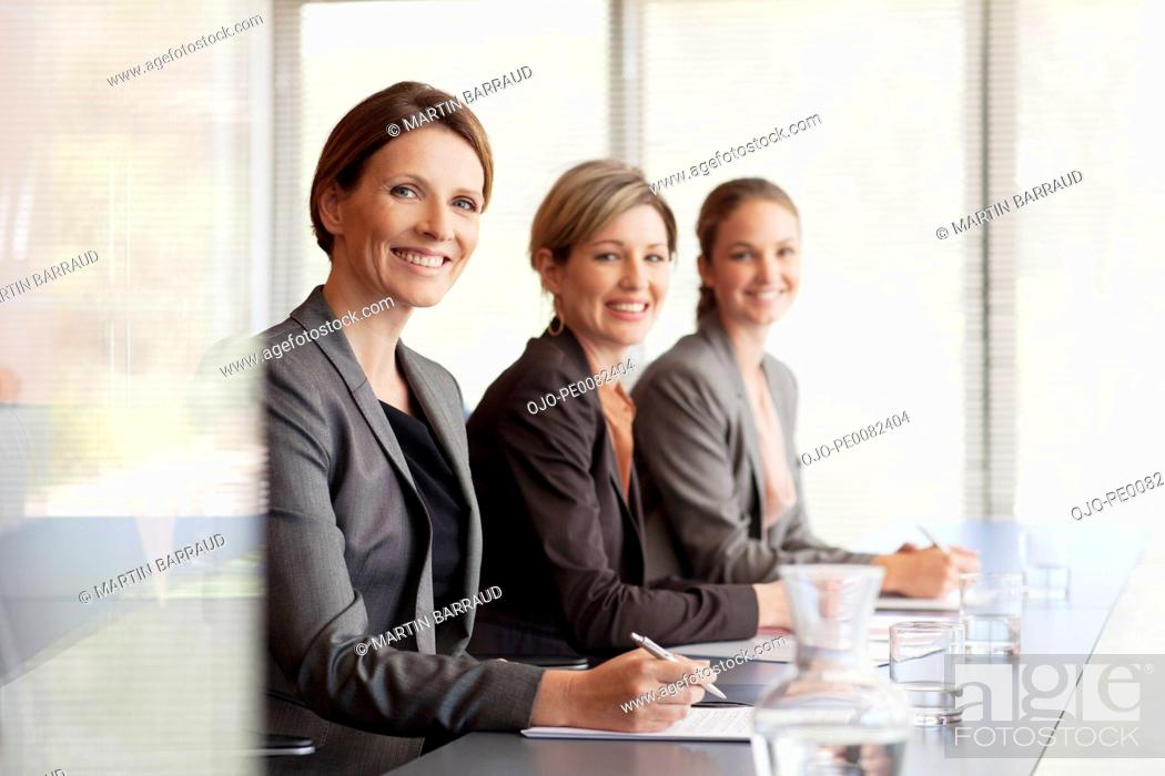Stock Photo: Portrait of smiling businesswomen sitting in a row in conference room.