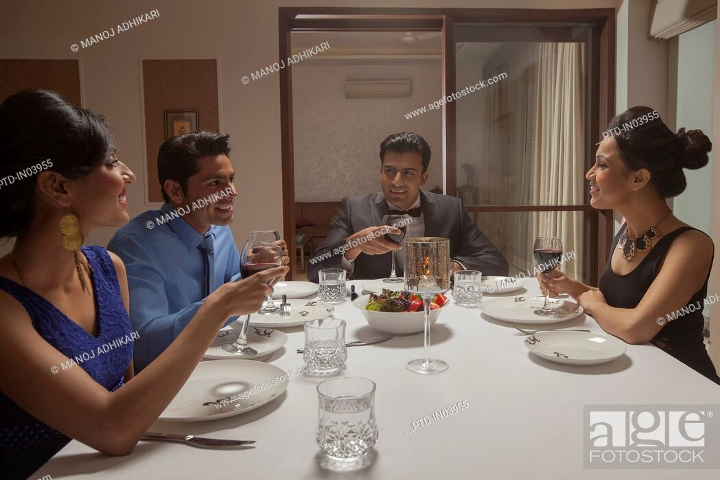 Stock Photo: India, Friends in formalwear having dinner party.