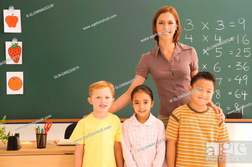 Stock Photo: Portrait of a female teacher standing with her three students in a classroom.