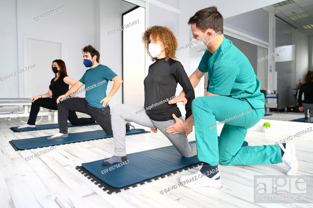 Stock Photo: Group of doctor and patients in a rehab center wearing facemasks while doing their physiotherapy. High quality photo.