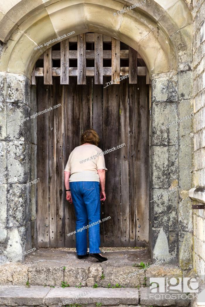 Imagen: nosey woman. . looking through cracks in medieval door. Southampton City Walls England UK.