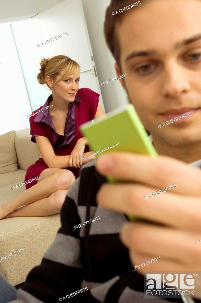 Stock Photo: Close-up of a young man holding an MP3 player with a young woman sitting behind him.