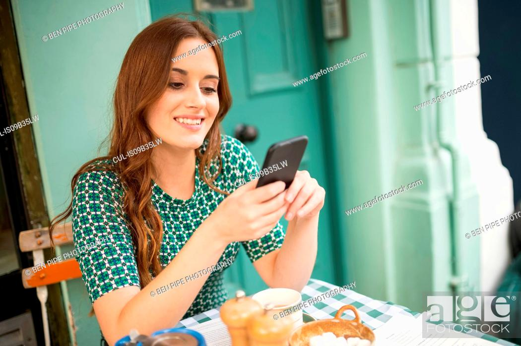 Stock Photo: Woman at pavement cafe looking at smartphone smiling.