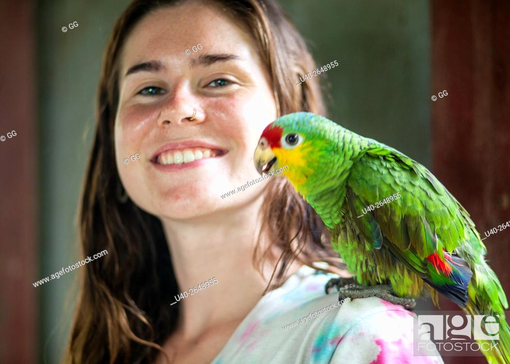 Stock Photo: Guatemala, Rio Dulce, young woman with parrot.