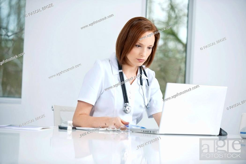 Stock Photo: Female doctor sitting in an office inserting CD into a laptop.