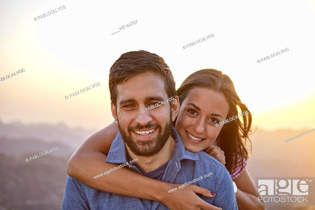Stock Photo: Happy young couple posing for a picture with a hazy mountainous background and happy smiles while wearing casual clothing.