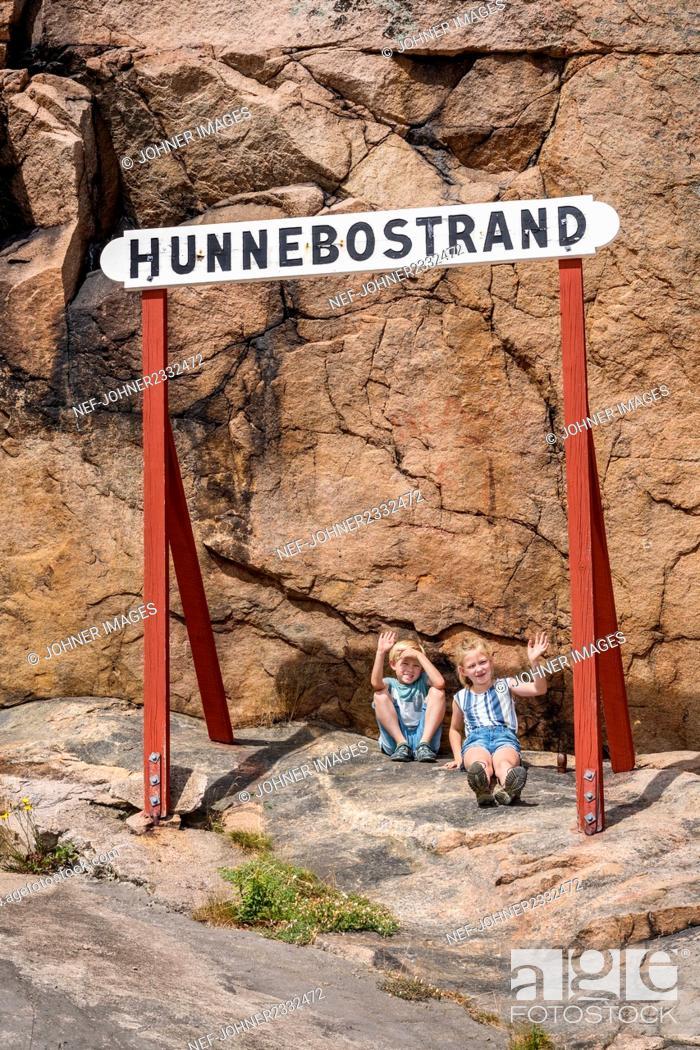 Photo de stock: Children sitting under sign, Hunnebostrand, Gotaland, Sweden.