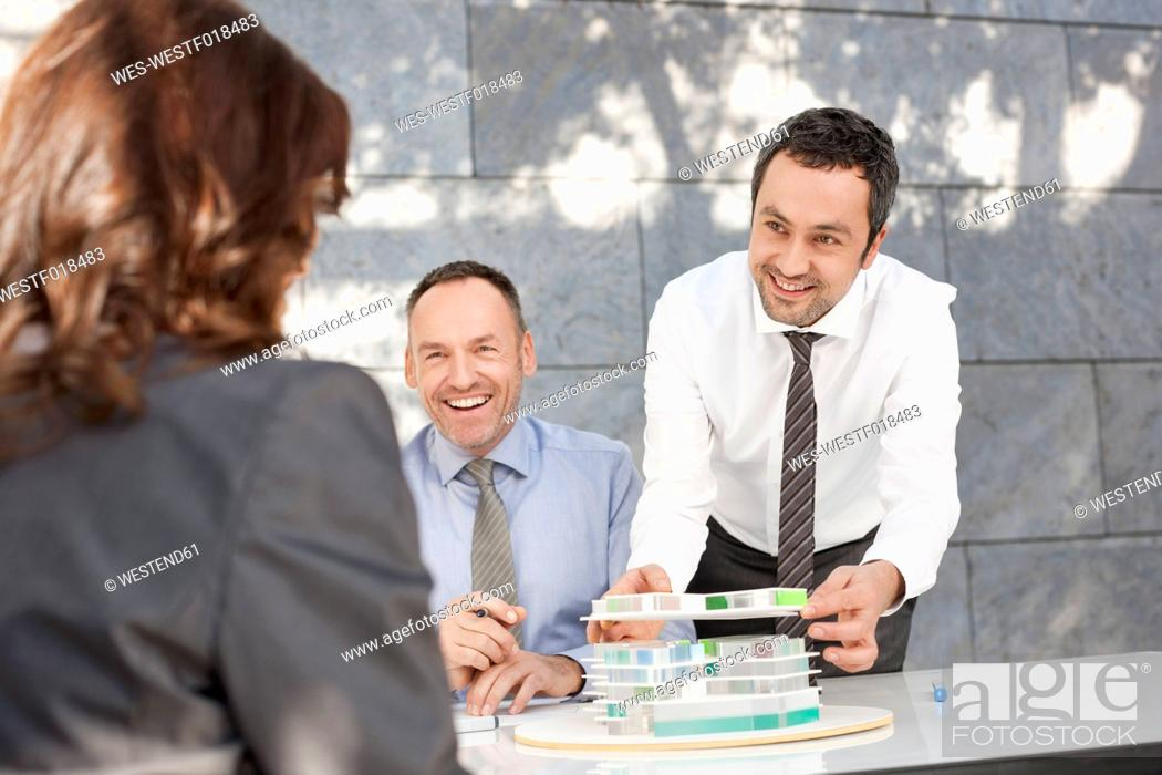 Stock Photo: Germany, Leipzig, Business people discussing about architectural model, smiling.