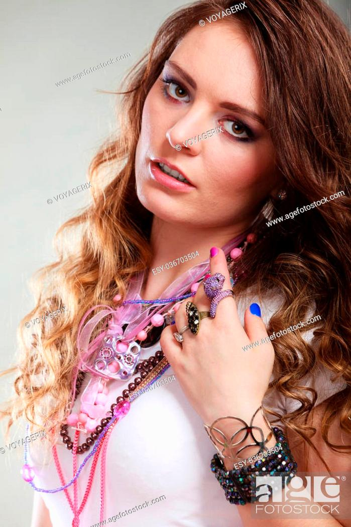 Stock Photo: Pretty young woman wearing many plenty of jewelry necklaces beads, rings and bracelets. Portrait of gorgeous fashion girl in studio on gray.