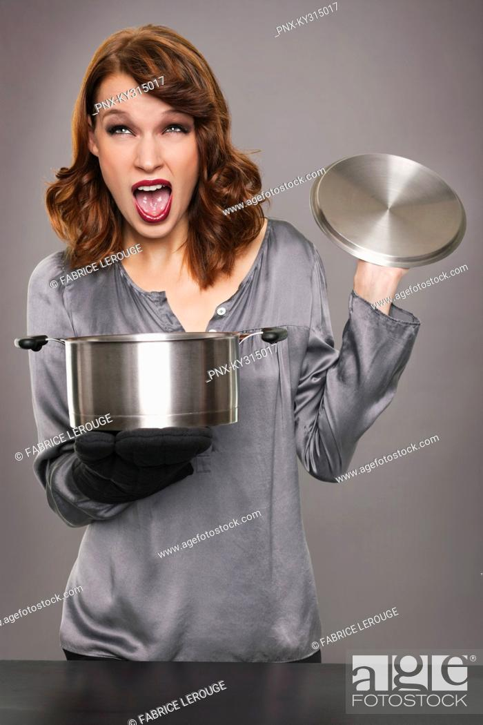 Stock Photo: Young woman looking at content of stew pot.
