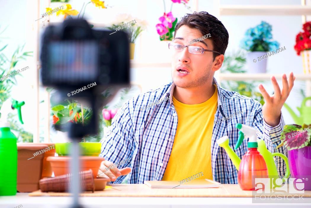 Stock Photo: Man florist gardener vlogger blogger shooting video on camera.