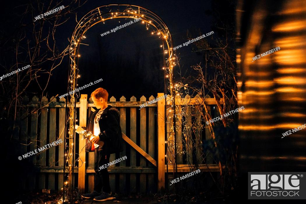 Stock Photo: Boy putting up Christmas lights at garden fence.