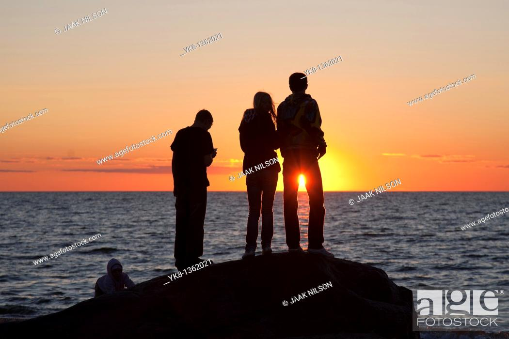 Stock Photo: People Silhouettes at Sunset on Beach.
