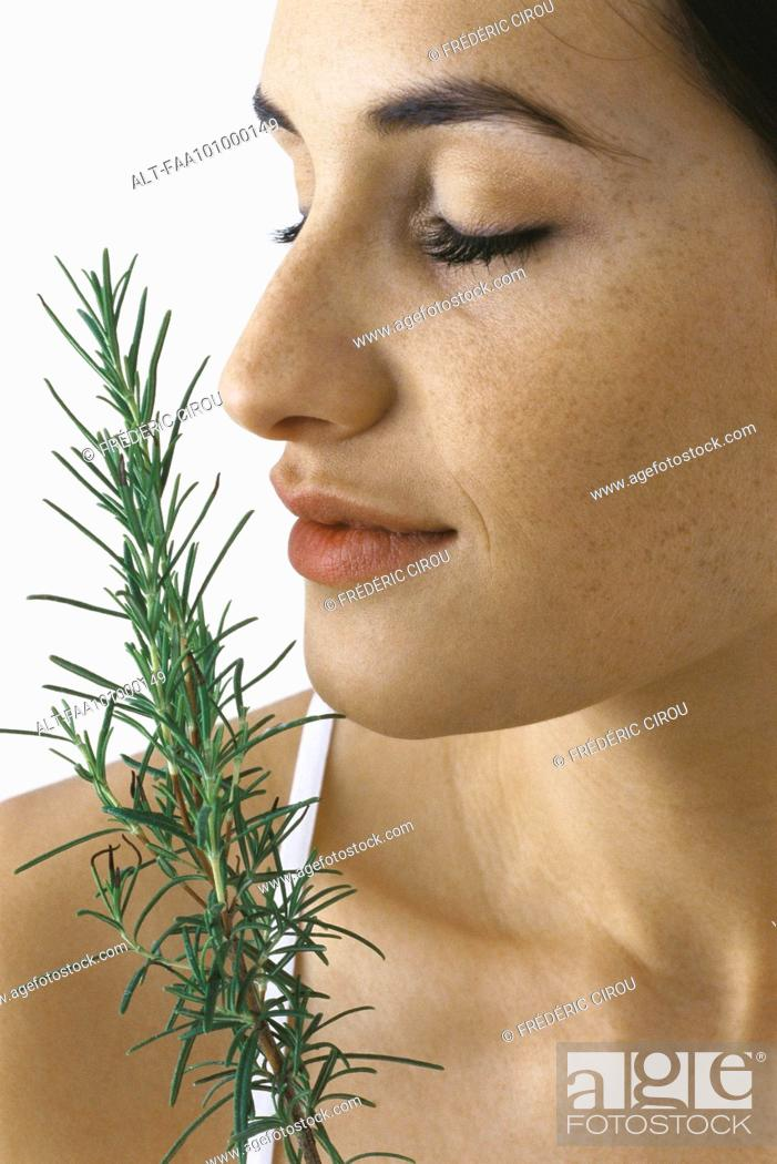Stock Photo: Young woman smelling spring of fresh rosemary, eyes closed.