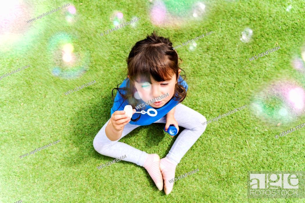 Stock Photo: Portrait of little girl blowing soap bubbles.