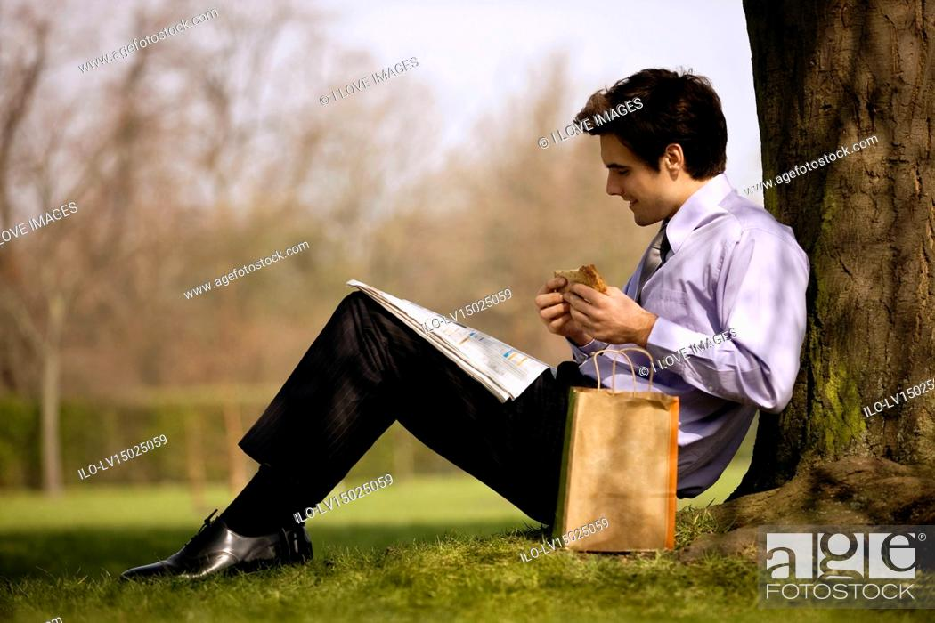 Stock Photo: A businessman leaning against a tree, eating a sandwich and reading the newspaper.
