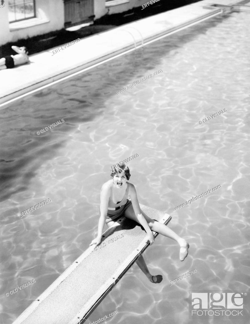 Stock Photo: High angle view of a woman sitting on a diving board and looking feared All persons depicted are not longer living and no estate exists Supplier warranties that.