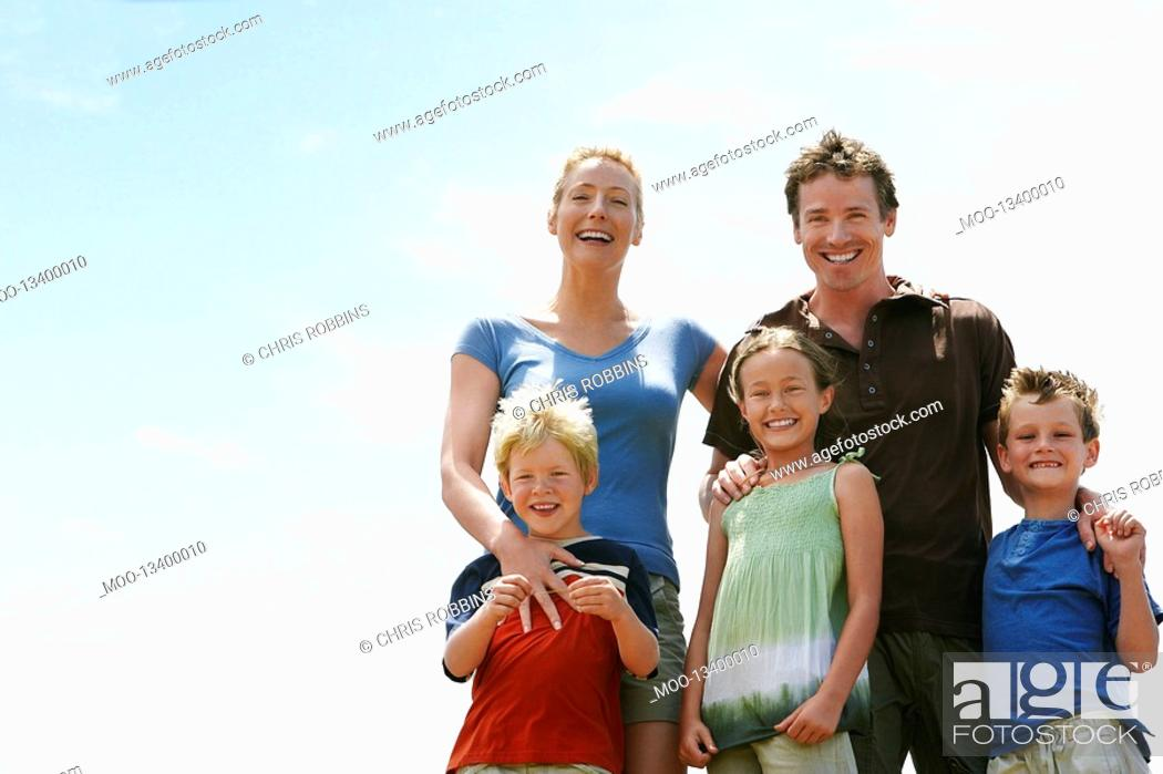 Stock Photo: Three children 7-9 with parents outdoors low angle portrait.