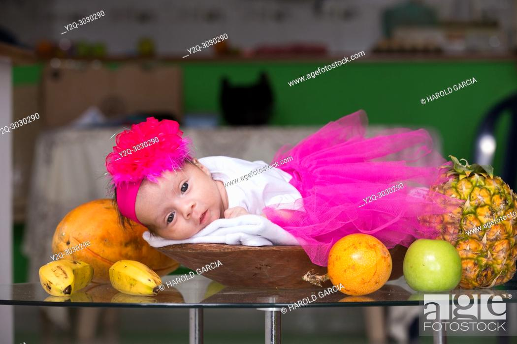 Imagen: Baby lying in a basket of fruit on the table.