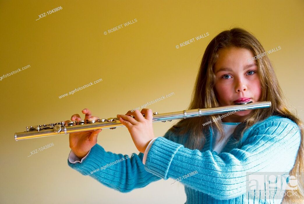Stock Photo: A young female music student playing the flute.
