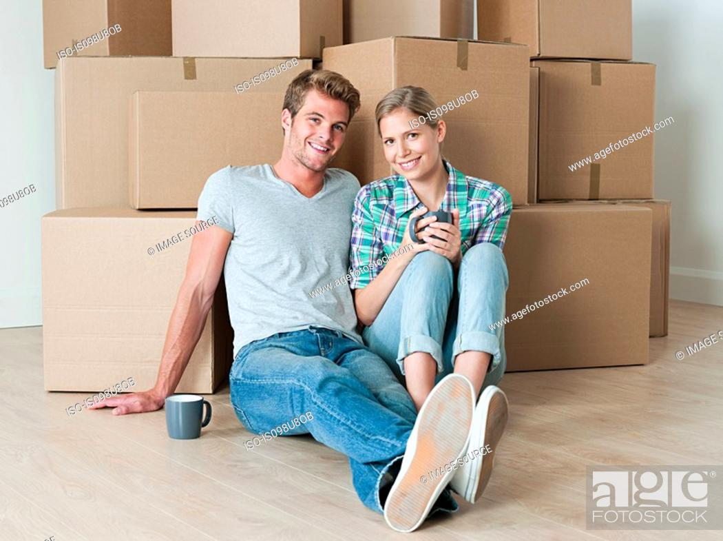 Stock Photo: Young couple taking a break from unpacking.