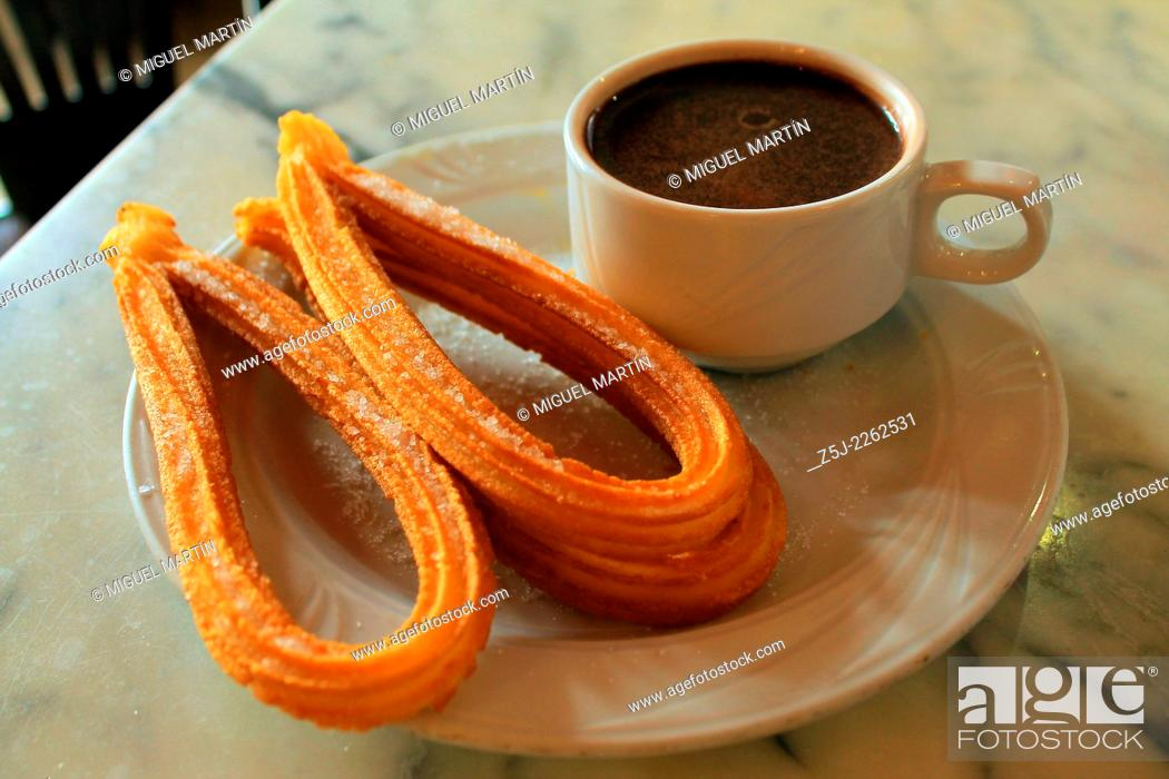 Stock Photo: Some churros sprinkled with sugar and served with thick hot chocolate, a typical fried-dough pastry breakfast or snack in Madrid and many other Spanish regions.