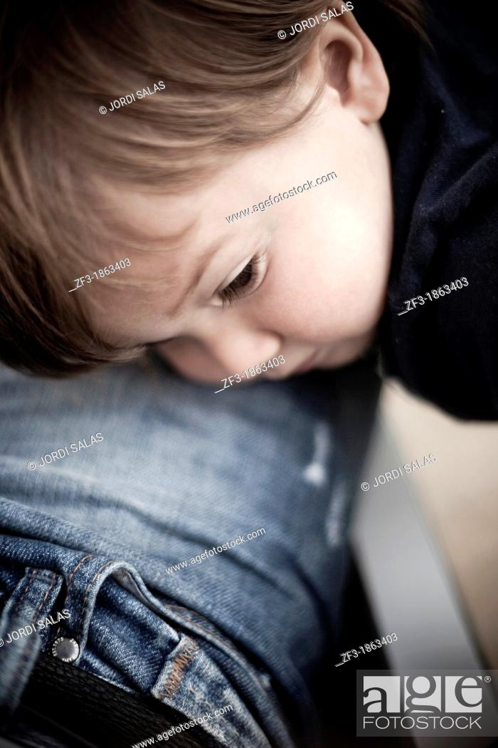 Stock Photo: One year old boy laying on his father leg.
