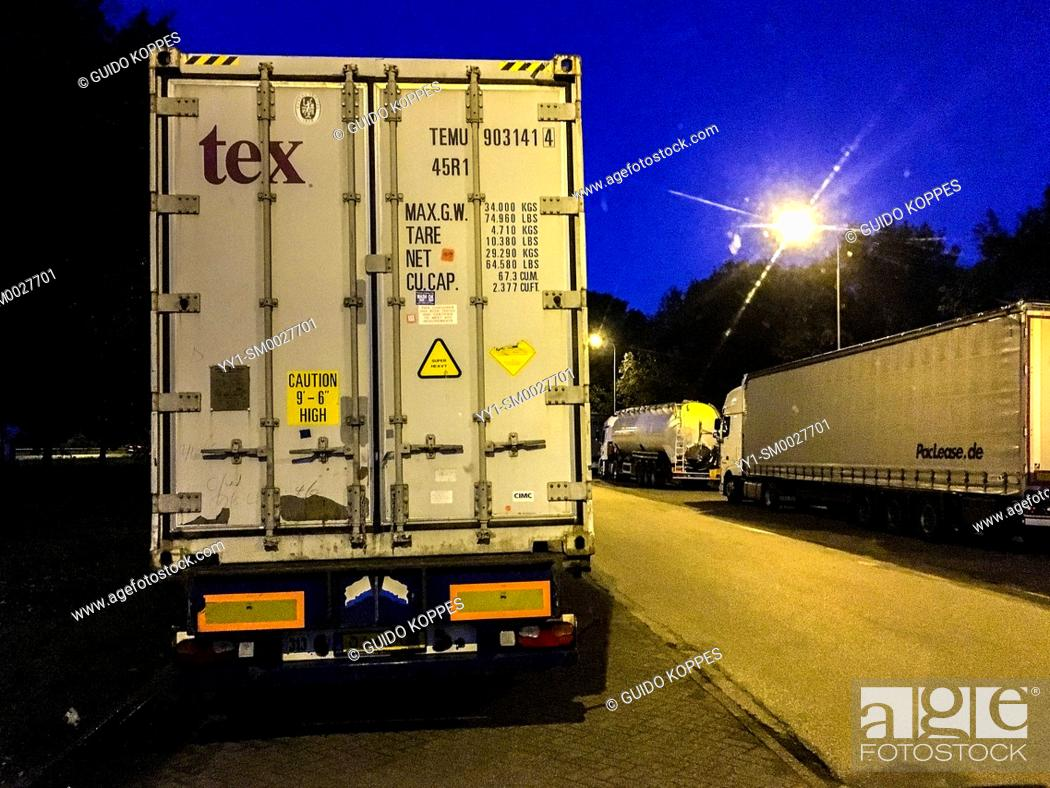 Stock Photo: Breda, Netherlands. Trucks and Freights parked alonside a highway parking lot and resting place during night, so drivers can sleep and taker ther mandotory rest.
