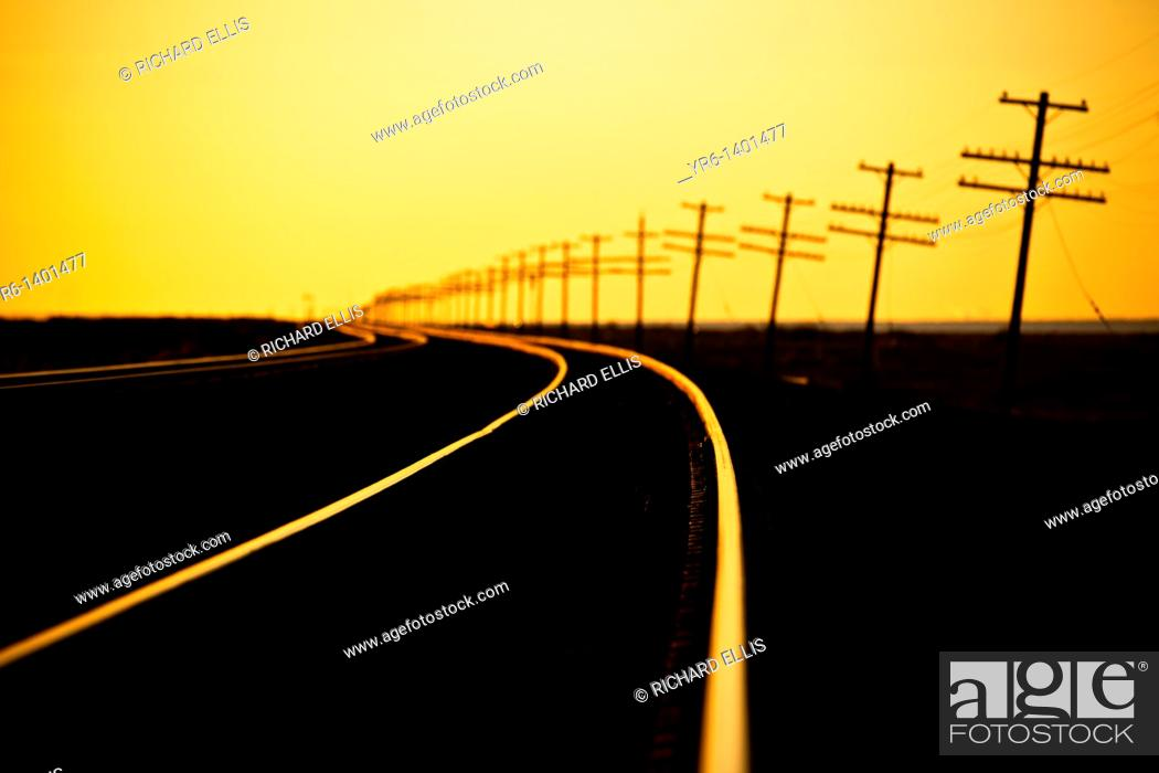 Stock Photo: Endless line of telephone poles along rail road tracks at sunrise Imperial Valley, CA.