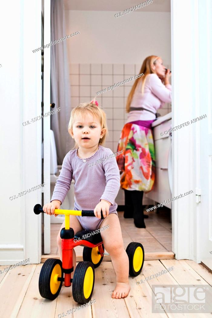 f61310fff04 Toddler girl playing on tricycle, mother in background, Stock Photo ...