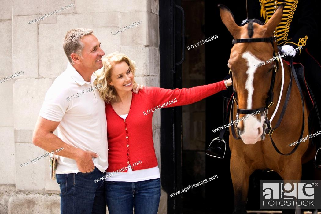 Stock Photo: A middle-aged couple standing at Horse Guards, woman stroking a horse.