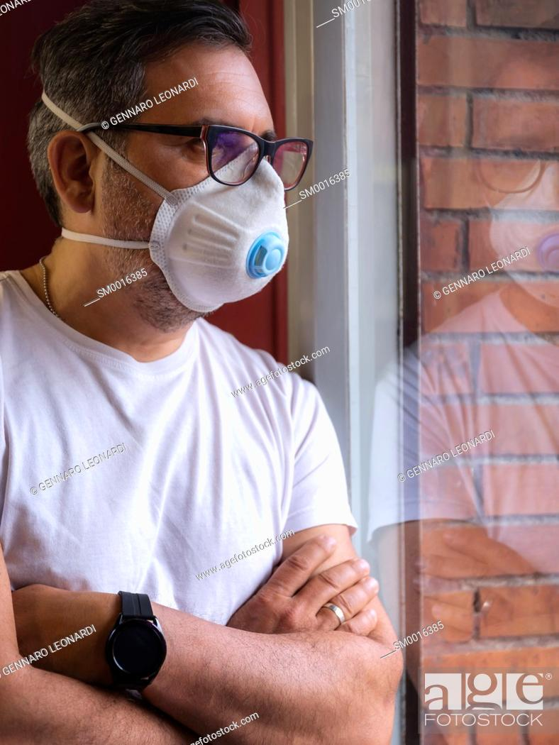Stock Photo: A man with a protective medical mask waits for the end of the covid-19 emergency quarantine, behind the glass of his home window.