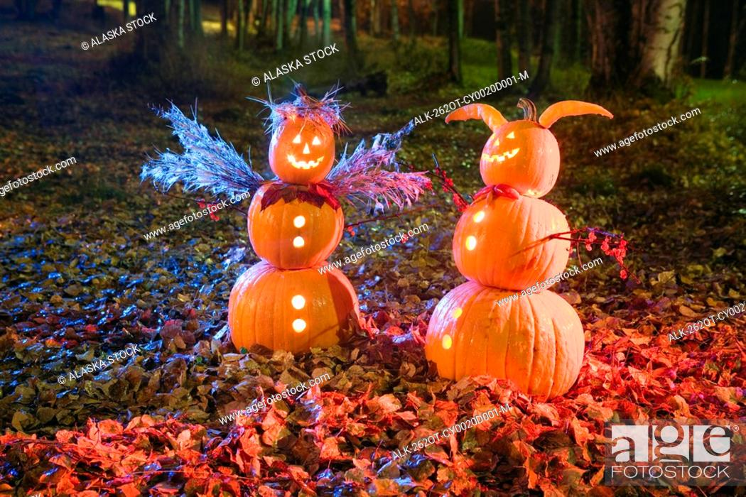 Stock Photo: Two Jack-O-Lantern people, one angel & one devil, standing in a forest & fallen leaves on the ground at twilight during Fall in Anchorage, Alaska.