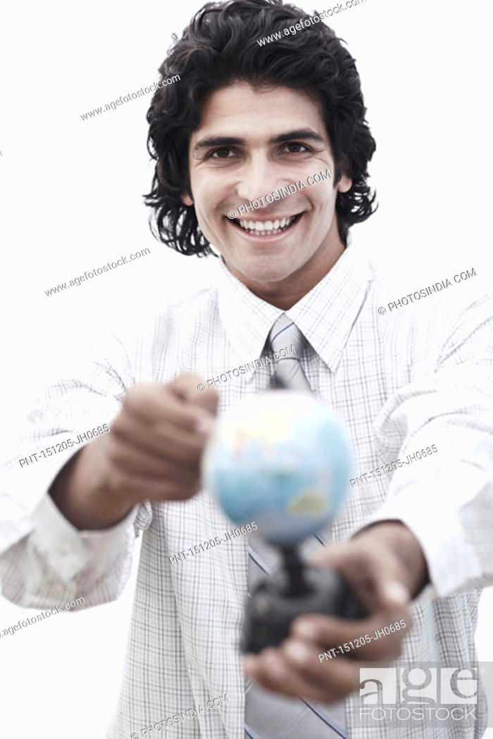 Stock Photo: Portrait of a businessman pointing to a globe.