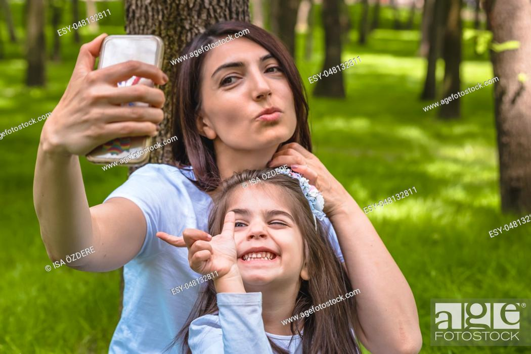 Stock Photo: Young mom and little girl takes selfie together. Happy mother and daughter moments with love and natural emotion. Photo of young mother and her daughter having.