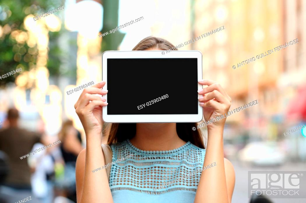 Stock Photo: Woman covering her face with a blank tablet screen showing display.
