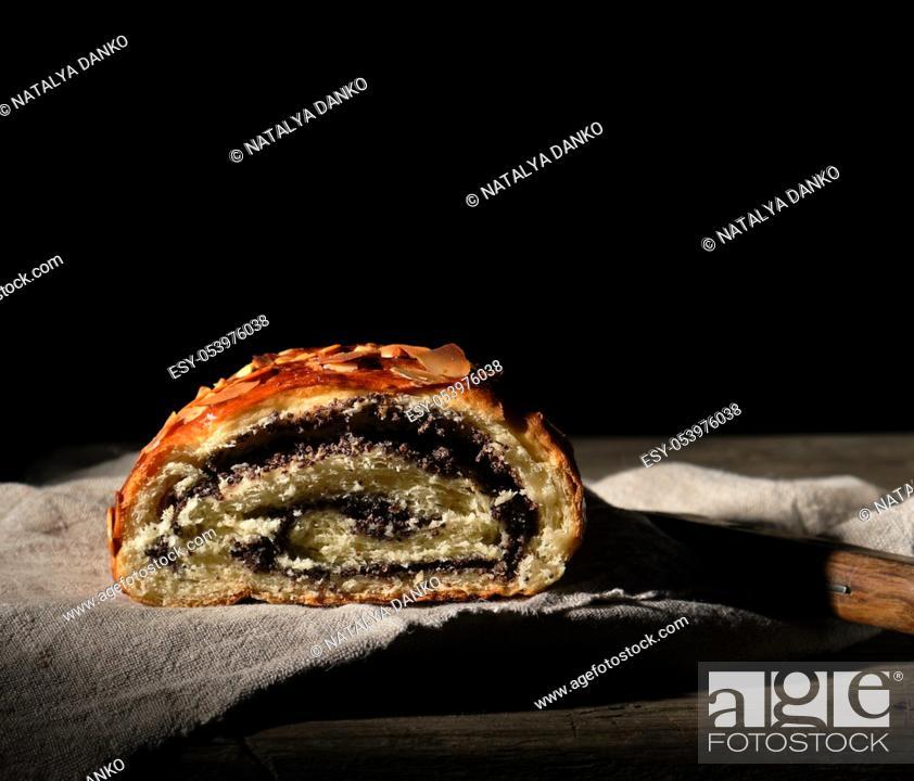 Stock Photo: baked roll with poppy seeds on gray linen napkin, dark background.