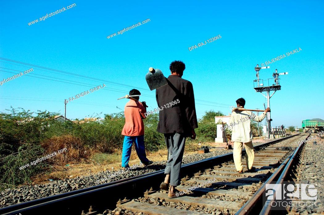 Stock Photo: Workers walking in Meterguage railway tracks and signal ; Gujarat ; India.