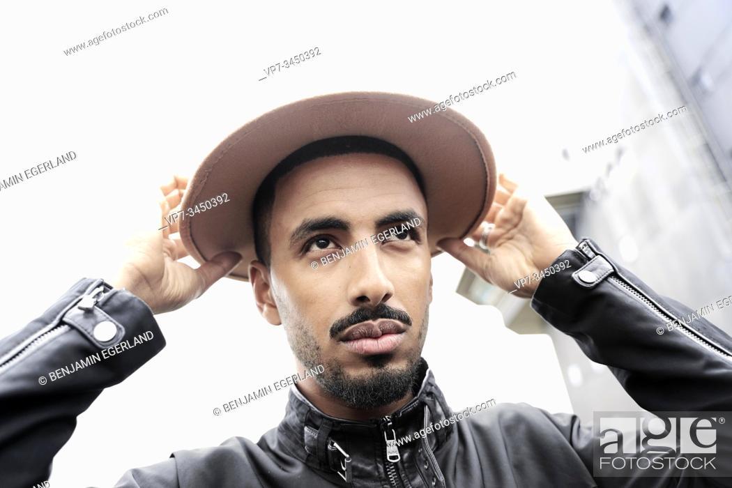 Stock Photo: Man adjusting brim of hat.