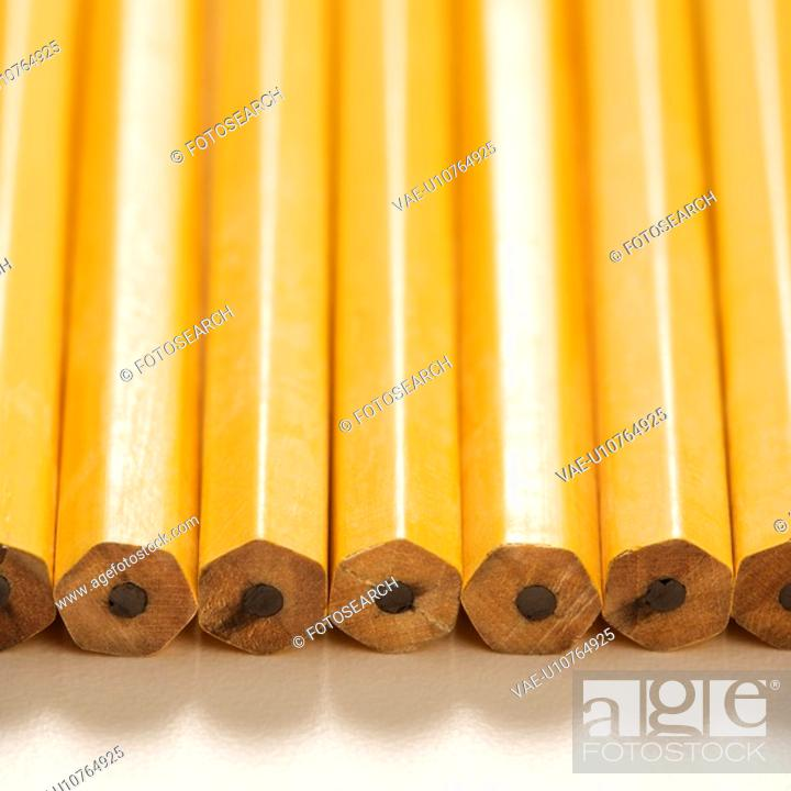 Stock Photo: Close up of group of new unsharpened pencils lined up in an even row.
