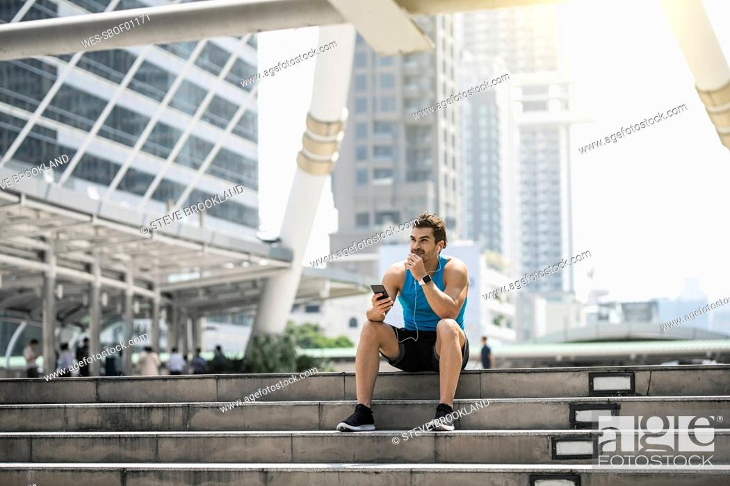 Stock Photo: Runner wearing earphones, checking messages on his smartphone.