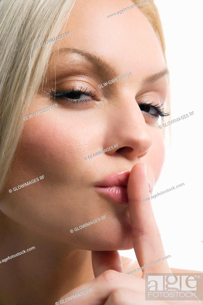 Stock Photo: Portrait of a young woman with her finger on her lips.