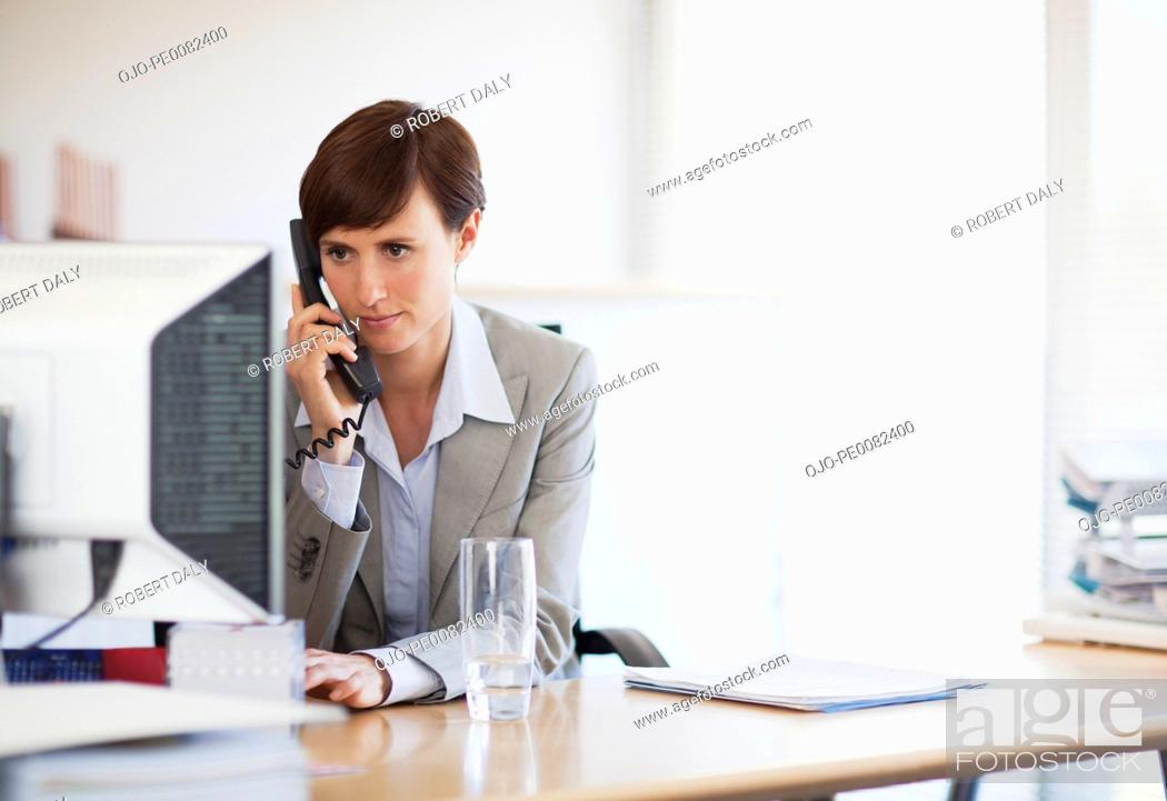 Stock Photo: Businesswoman talking on telephone and working at computer in office.